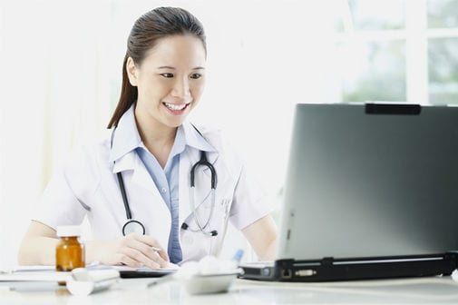 Female doctor smiling while using laptop